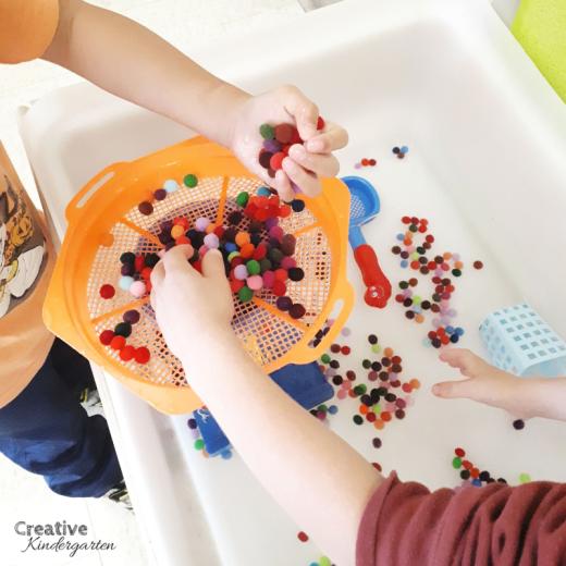 Water and pompom sensory bin for kindergarten fun, hands-on activity.